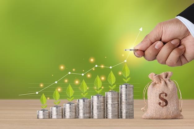 Biznesmen ręcznie układający monety rosnące i rosnące rośliny z wykresem wzrostu i torbą na pieniądze na drewnianym stole