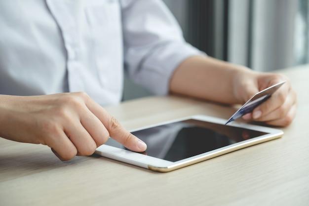 Biznesmen ręcznie używać tabletu i trzymać kartę kredytową, aby robić zakupy online z domu, wydawać pieniądze