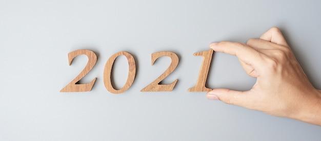 Biznesmen ręcznie zmienia drewniany numer 2020 na 2021