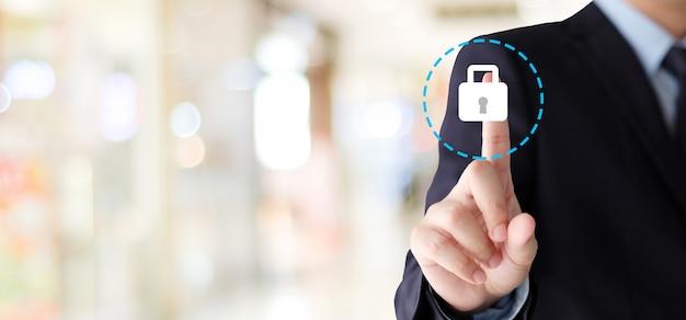 Biznesmen ręka dotyka cyber ochrony ikonę nad plamy tłem