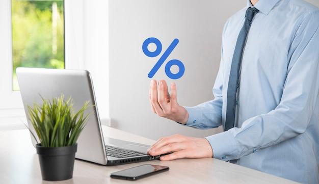 Biznesmen ręka ma ikonę symbolu procentu. koncepcja stóp procentowych finansowych i hipotecznych.