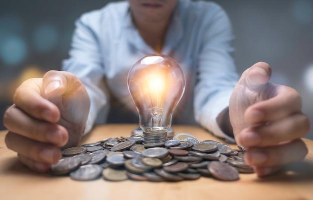 Biznesmen ręka ochrony sterty monet i żarówka, które świecące. kreatywnie nowy biznesowy pomysł może zarabiać pieniądze.