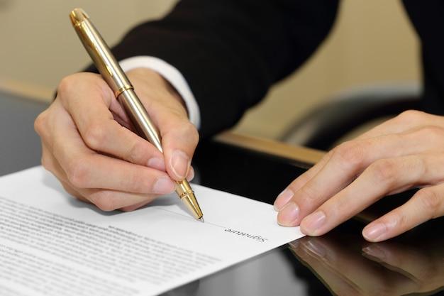 Biznesmen ręka podpisuje kontraktowego papier