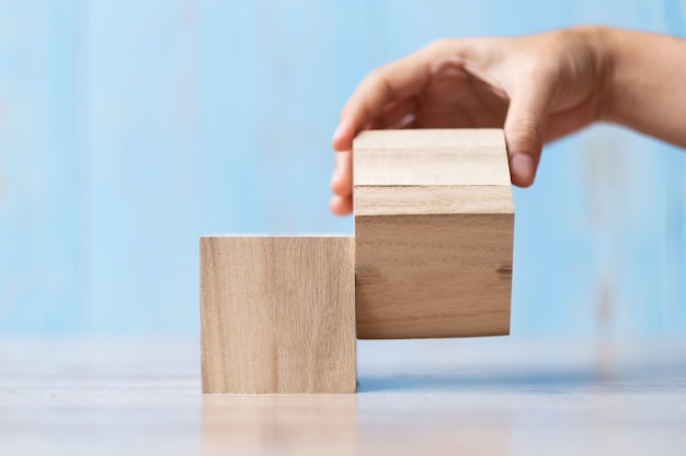 Biznesmen ręka podrzuca drewnianego blok na stole