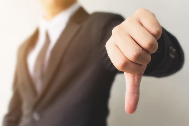 Biznesmen ręka pokazuje kciuka puszka znaka gest. niechęć lub zła koncepcja