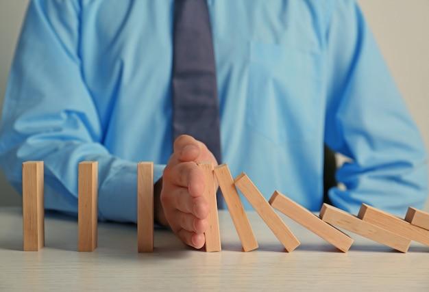 Biznesmen ręka próbuje zatrzymać obalanie kostki domino na stole