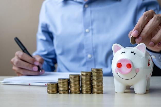 Biznesmen ręka stawia złotą monetę na prosiątko bankowości