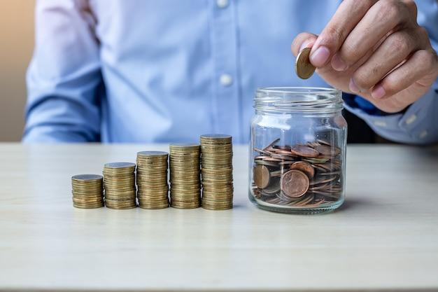 Biznesmen ręka stawia złotą monetę na szklanym słoju