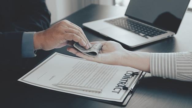 Biznesmen ręka trzyma banknot dolara pieniędzy, aby przekupić koncepcję przeciwdziałania przekupstwu urzędników finansowych