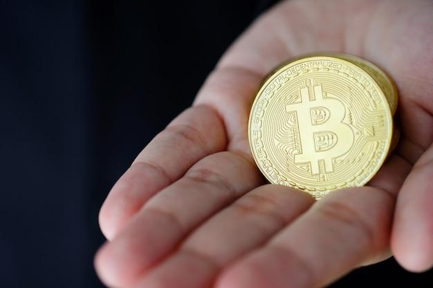 Biznesmen ręka trzyma bitcoiny, kryptowalutę i pojęcie blockchain