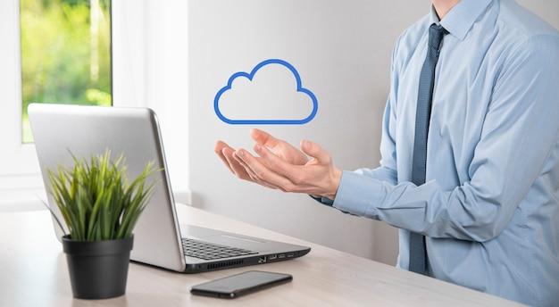 Biznesmen ręka trzyma chmurę. koncepcja przetwarzania w chmurze, z bliska młody człowiek biznesu z chmury nad jego ręką. pojęcie usługi w chmurze.