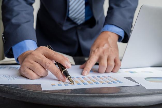 Biznesmen ręka trzyma długopis analizuje wykres z laptopem w domowym biurze
