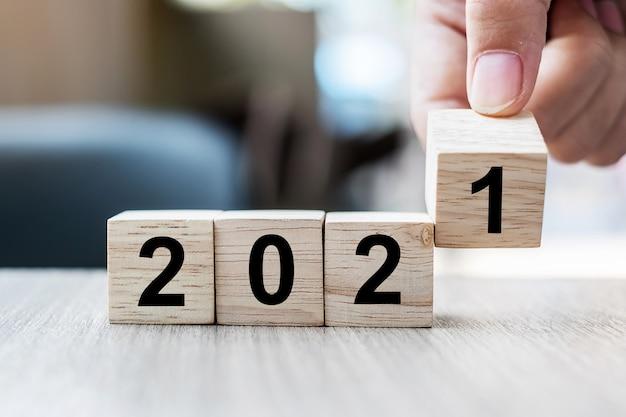 Biznesmen ręka trzyma drewnianą kostkę ze słowem bloku 2021 na stole