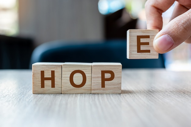 Biznesmen ręka trzyma drewnianego sześcianu blok z nadziei biznesowym słowem na stołowym tle.