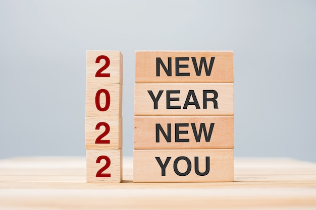 Biznesmen ręka trzyma drewniany blok z tekstem 2022 nowy rok nowy rok na tle tabeli. koncepcje rozdzielczości, strategii, celu, biznesu i wakacji