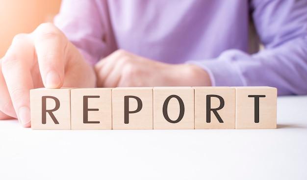 Biznesmen ręka trzyma drewniany sześcian blok z biznesowym słowem raport na stole