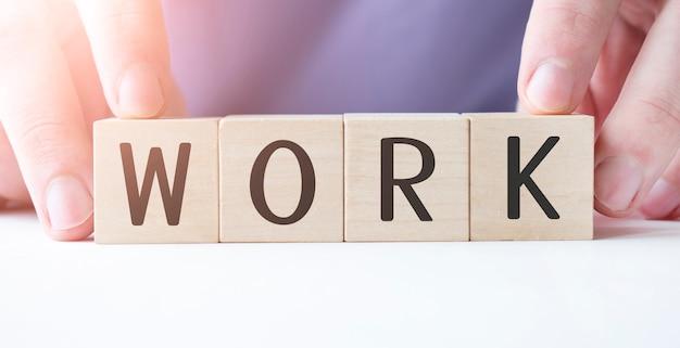Biznesmen ręka trzyma drewniany sześcian blok ze słowem biznes praca na tle tabeli. misja, wizja i koncepcja podstawowych wartości