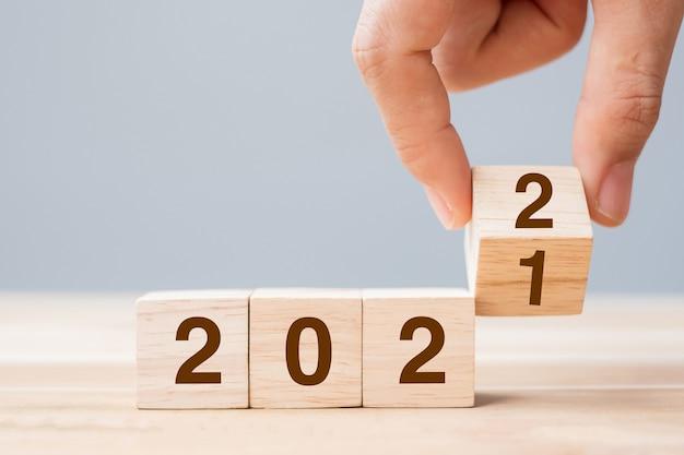 Biznesmen ręka trzyma drewniany sześcian z odwróć tekst bloku 2021 do 2022 na tle tabeli. koncepcje rozdzielczości, strategii, rozwiązania, celu, biznesu i świąt sylwestrowych