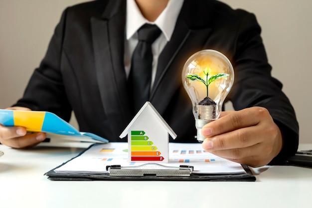 Biznesmen ręka trzyma energooszczędną żarówkę z roślinami rosnącymi na monetach w żarówkach