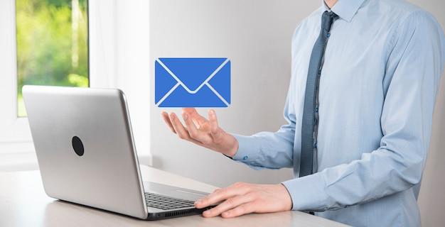 Biznesmen ręka trzyma ikonę e-mail, skontaktuj się z nami przez e-mail biuletyn i chroń swoje dane osobowe przed spamem. centrum obsługi klienta skontaktuj się z nami koncepcja.