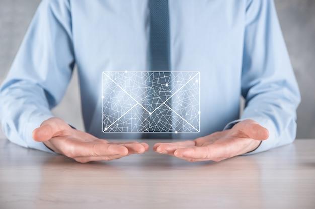 Biznesmen ręka trzyma ikonę e-mail, skontaktuj się z nami przez e-mail z biuletynem i chroń swoje dane osobowe przed spamem. centrum obsługi klienta skontaktuj się z nami koncepcja.