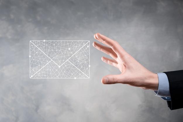 Biznesmen ręka trzyma ikonę e-mail, skontaktuj się z nami przez e-mail z biuletynem i chroń swoje dane osobowe przed spamem.