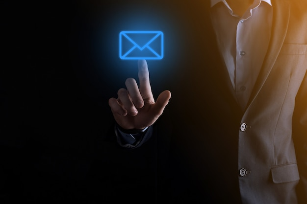 Biznesmen ręka trzyma ikonę e-mail, skontaktuj się z nami przez e-mail z biuletynem i chroń swoje dane osobowe