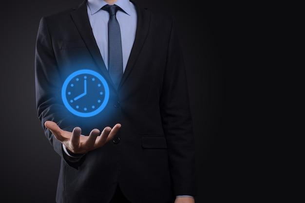 Biznesmen ręka trzyma ikonę zegara godzin ze strzałką. szybka realizacja pracy.zarządzanie czasem biznesowym i czasem biznesowym to pojęcia pieniądza.