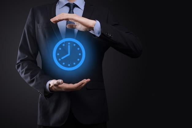 Biznesmen ręka trzyma ikonę zegara godzin ze strzałką. szybka realizacja pracy. zarządzanie czasem i czasem biznesowym to pojęcia pieniędzy.