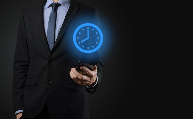 Biznesmen ręka trzyma ikonę zegara godzin ze strzałką. szybka realizacja pracy