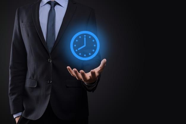 Biznesmen ręka trzyma ikonę zegara godzin ze strzałką