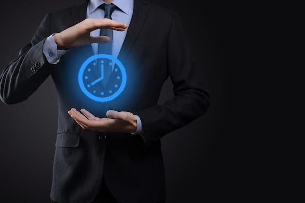 Biznesmen ręka trzyma ikonę zegara godzinowego ze strzałką. szybka realizacja prac. zarządzanie czasem w biznesie i czas biznesowy to koncepcje pieniądza.