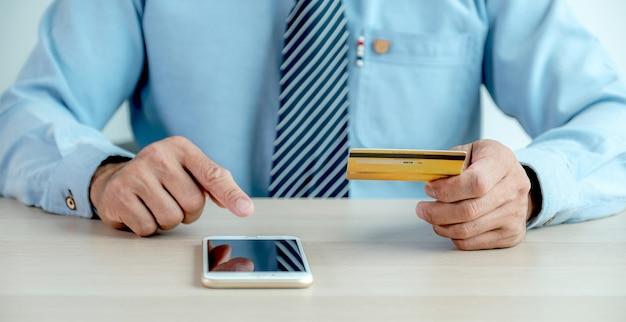 Biznesmen ręka trzyma kartę kredytową i używa smartfona do zakupów online z domu, płatności e-commerce, bankowości internetowej, wydawania pieniędzy na następne wakacje.