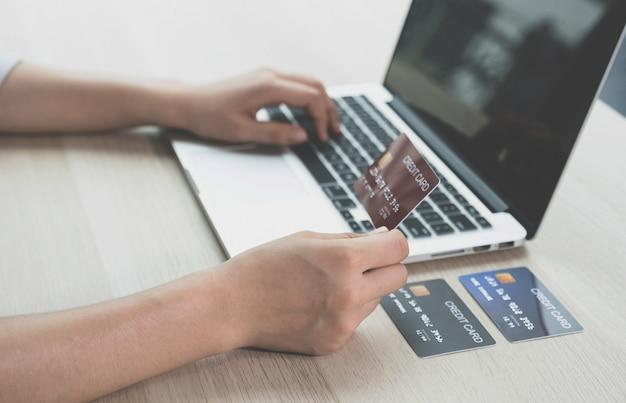 Biznesmen ręka trzyma kartę kredytową na zakupy online na komputerze przenośnym z domu, płatności e-commerce, bankowość internetową, wydawanie pieniędzy na następne wakacje.