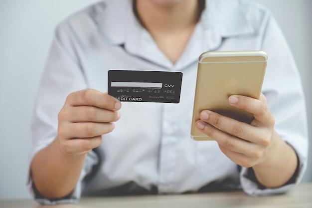 Biznesmen ręka trzyma kartę kredytową na zakupy online na smartfonie z domu, płatności e-commerce, bankowość internetową, wydawanie pieniędzy na następne wakacje.
