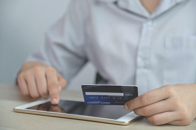 Biznesmen ręka trzyma kartę kredytową na zakupy online na tablecie z domu, płatności e-commerce, bankowość internetową, wydawanie pieniędzy na następne wakacje.