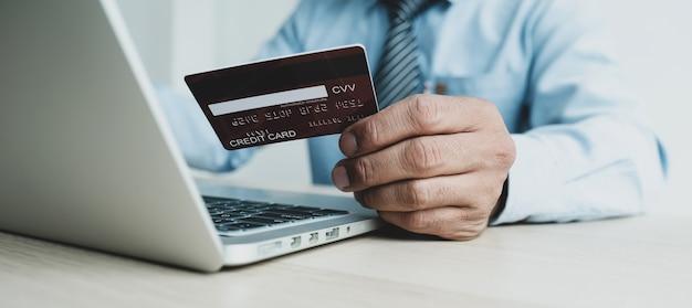 Biznesmen ręka trzyma kartę kredytową na zakupy online z domu za pomocą laptopa, płatności e-commerce, bankowość internetowa, wydawanie pieniędzy na następne wakacje.
