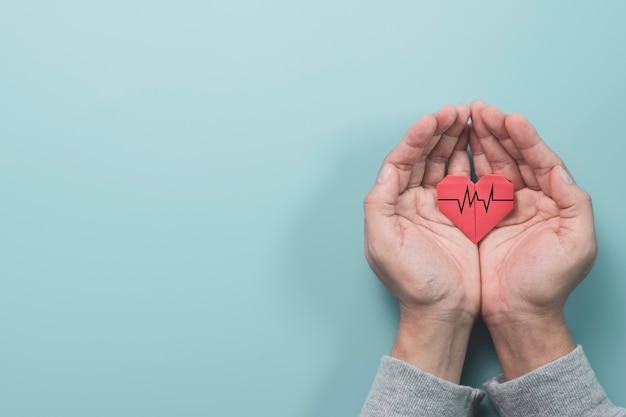 Biznesmen ręka trzyma papier czerwone serce z sygnałem fali serca na niebieskim tle. jest to koncepcja stanu zdrowia.