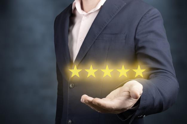 Biznesmen ręka trzyma pięć gwiazdek na niebieskim tle biznesmen ręka trzyma pięć gwiazdek. ocena 5 złotych gwiazdek