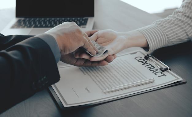Biznesmen ręka trzyma pieniądze banknotów dolarowych, aby przekupić urzędników finansowych przeciwko przekupstwu