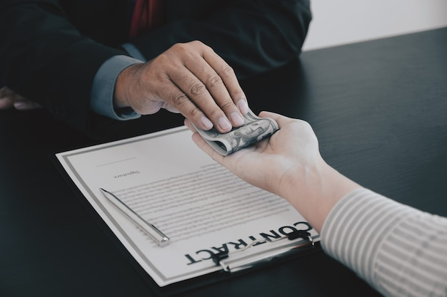 Biznesmen ręka trzyma pieniądze banknotów dolarowych, aby przekupić urzędników finansowych