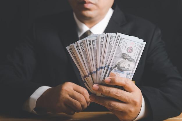 Biznesmen ręka trzyma pieniądze - dolarów amerykańskich. inwestycje, sukces i dochodowe koncepcje biznesowe