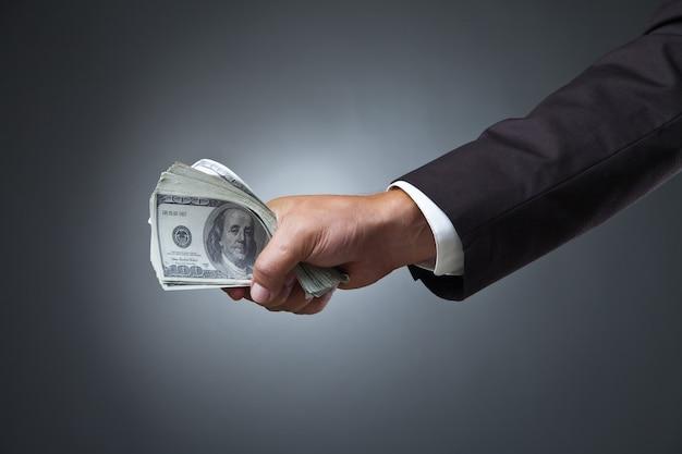Biznesmen ręka trzyma pieniądze na ciemności