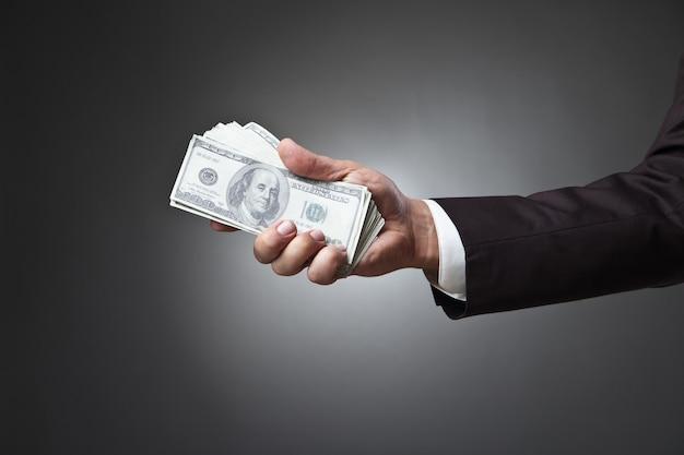 Biznesmen ręka trzyma pieniądze na ciemnym tle