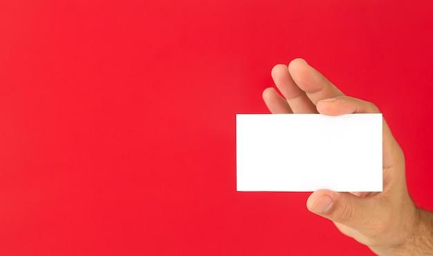 Biznesmen ręka trzyma pustą wizytówkę na czerwonym tle