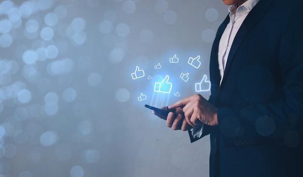 Biznesmen ręka trzyma smartphone i za pomocą aplikacji z podobną ikoną. udostępnianie w sieciach społecznościowych, aplikacje społecznościowe.