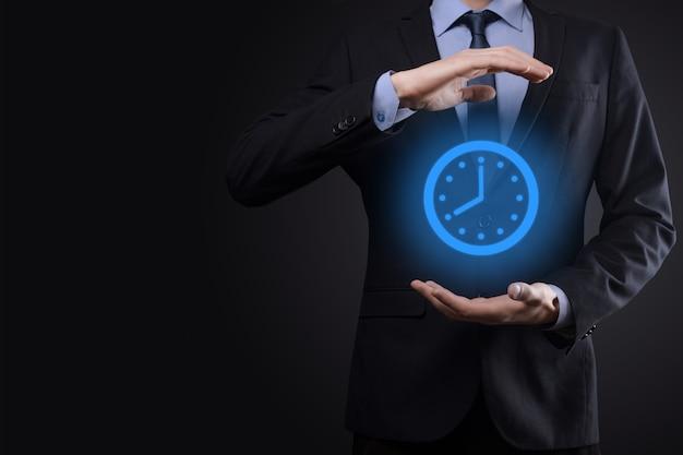Biznesmen ręka trzyma symbol zegara godzin ze strzałką. szybka realizacja pracy.zarządzanie czasem biznesowym i czasem biznesowym to pojęcia pieniądza.