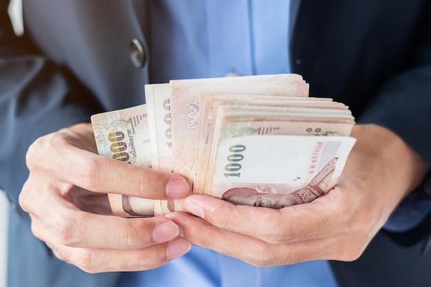 Biznesmen ręka trzyma tajlandzkiego bahta banknotu stertę.