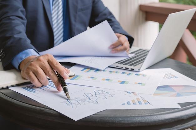 Biznesmen ręka trzyma wykres analizy pióra z laptopem w domowym biurze do ustalania celów biznesowych