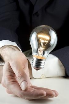 Biznesmen ręka trzyma żarówkę